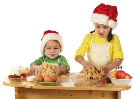 ni�os cocinando: Ni�os peque�os que se cocina el pastel de Navidad Foto de archivo