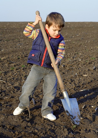 shovel in dirt: Little boy to dig on field with big shovel