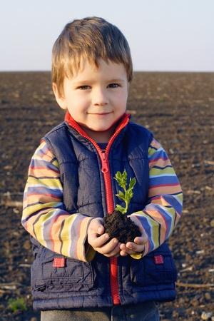 farm boys: Smiling little boy on field holding the plant