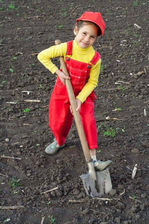 Portrait of smiling little girl with big shovel on the field photo