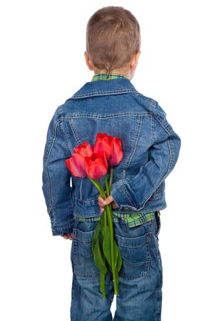 flowers boy: Little boy hiding red tulips behind his Stock Photo