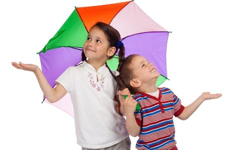 Two little children holding colored umbrella and checking for rain Stock Photo