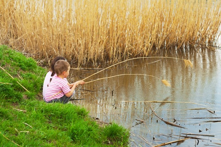 Two little fishermans on the coast with a stem reeds photo