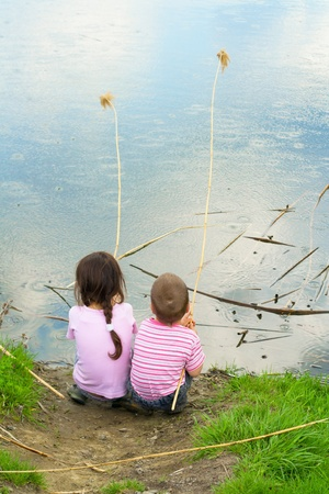 Two little fishermans on the coast with a stem reeds sitting in the rain photo
