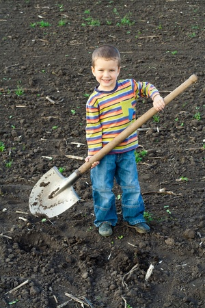 farm boys: Portrait of little children with big shovel in the field