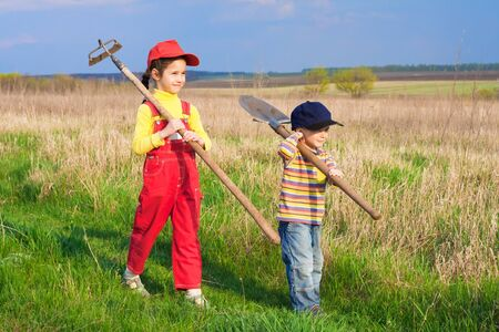 children walking: Two little children walking on field with garden tools Stock Photo