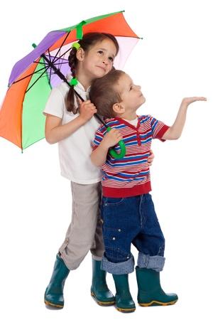 botas de lluvia: Dos niños pequeños sosteniendo paraguas de colores y mirando hacia arriba Foto de archivo