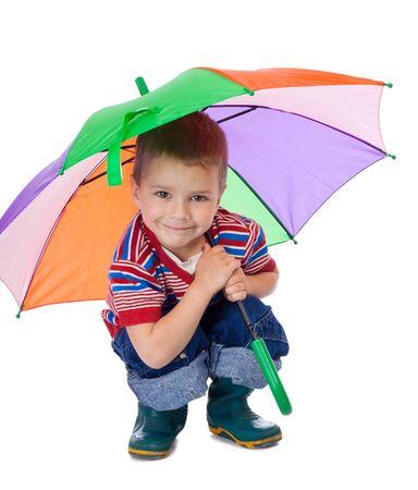 Little boy sitting under colored umbrella photo