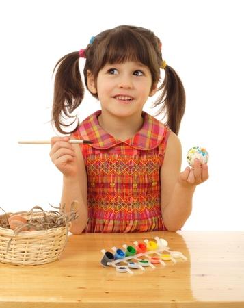 Little girl painting the easter eggs photo