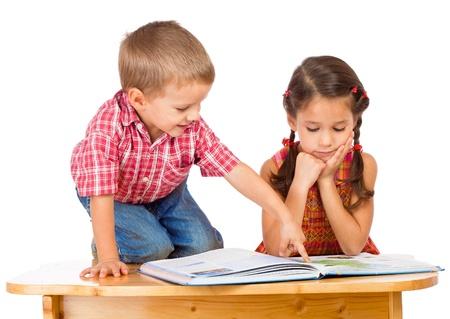 ni�os leyendo: Dos sonrientes a ni�os leyendo el libro sobre la mesa, aislada en blanco Foto de archivo