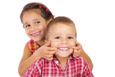 smiling: Two funny smiling little children, showing their teeth, isolated on white