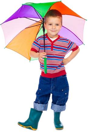 botas de lluvia: Niño sonriente con colores paraguas, aislado en blanco Foto de archivo