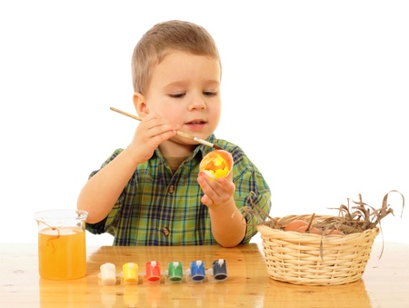 Little child painting the easter eggs photo