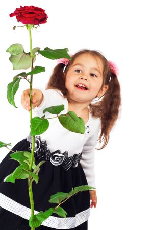 Smiling little girl stretching forward red rose Stock Photo - 10000473