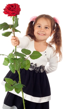 Smiling little girl stretching forward red rose Stock Photo - 10000497