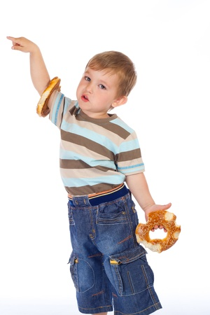 Little boy with two bitten bagels and empty pointing hand photo