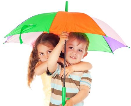 proteccion: Dos niños bajo el paraguas color Foto de archivo