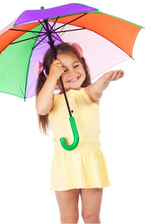 Little smiling girl holding colored umbrella and checking for rain photo