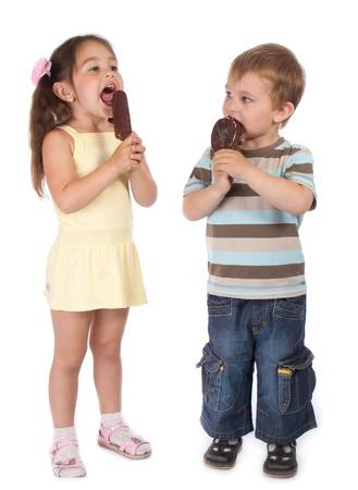 licking in isolated: Due in piedi piccoli bambini a mangiare il gelato al cioccolato
