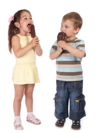 dirty girl: Two standing little children eating chocolate ice cream Stock Photo