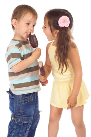 Two little children eating chocolate ice cream