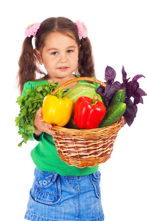 Little girl with basket of vegetables, isolated on white photo