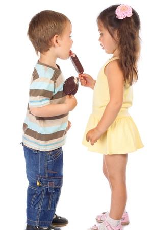 licking in isolated: Ragazzino mangiare il gelato al cioccolato della ragazza Archivio Fotografico