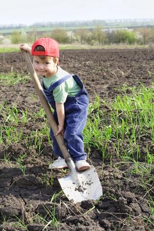 arando: Niño en el campo con una pala grande, mirando a la cámara
