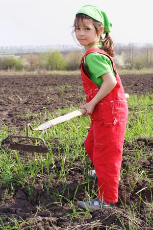 Little girl on field with chopper tool, looking to camera