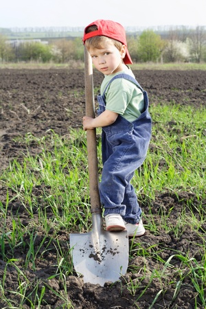 Little boy a cavar en campo con gran pala, mirando a la cámara
