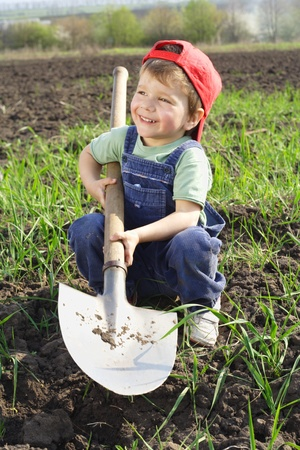 Smiling little boy sitting on field with shovel photo
