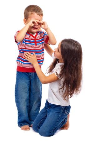 mujer arrodillada: Chica calmar a su hermanito llorando, aislados en blanco