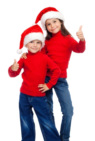 Two smiling little children with thumbs up sign and Santa photo