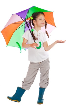 Little girl holding color umbrella, checking for rain, isolated on white Stock Photo