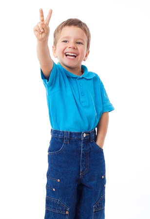 victory stand: Smiling little boy showing victory gesture, isolated on white