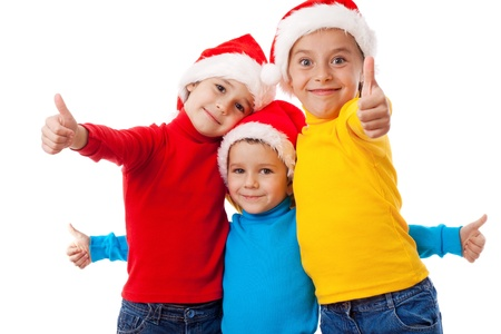 Three smiling children in Santa hats showing thumb up sign, isolated on white photo