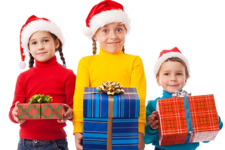 Three smiling kids in Santa hats with gift boxes, isolated on white photo