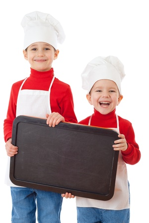 Smiling little cookers with empty chalkboard, isolated on white