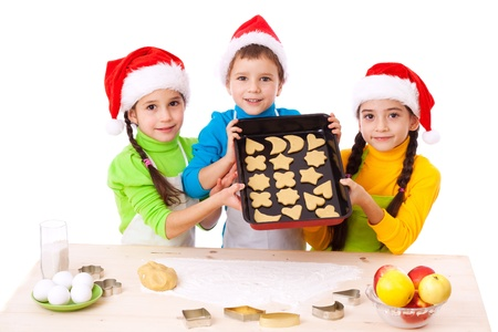 little dough: Three smiling children with Christmas cooking, isolated on white