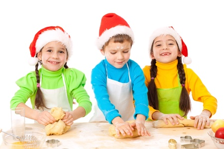 christmas cooking: Three smiling kids with Christmas cooking, isolated on white