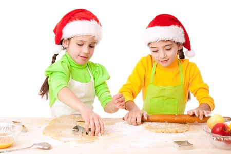 Two smiling girls with Christmas cooking, isolated on white photo