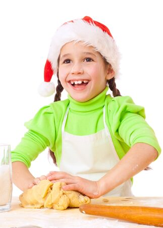 little dough: Smiling little girl kneading the dough for Christmas cooking, isolated on white Stock Photo
