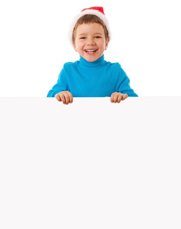 Smiling little boy in Santas hat with empty banner, isolated on white photo