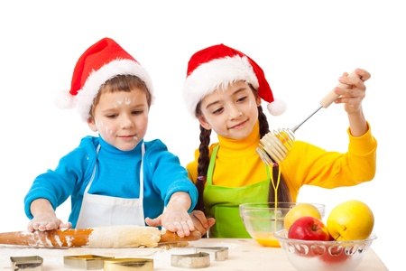 Two smiling children with Christmas cooking, isolated on white photo
