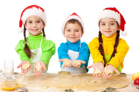 Three smiling kids showing Christmas cooking, isolated on white photo