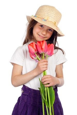 elementary age girl: Smiling little girl in straw holding in hands red tulips