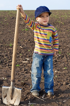 Portrait of little children with big shovel on the field Stock Photo - 11881748