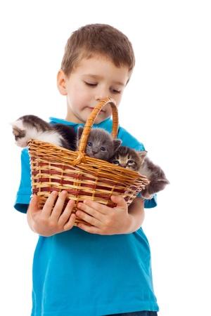 Niño con los gatitos en mimbre, aislado en blanco