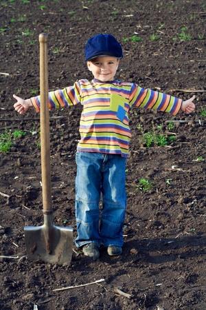 arando: Retrato de los niños pequeños con una pala grande en el campo