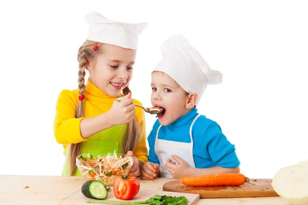 Two kids eating salad, isolated on white photo